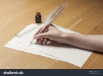 stock-photo-a-female-woman-hand-hold-write-a-feather-quill-pen-with-ink-on-the-letter-paper-and-wood-desk-240612316