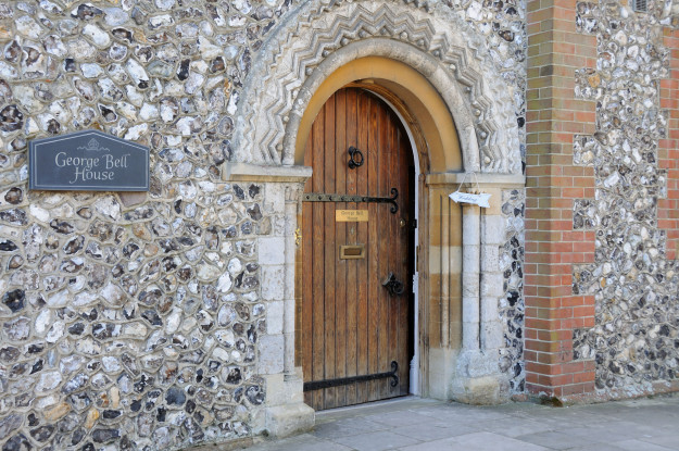 The entrance door to george bell house in chichester partly open